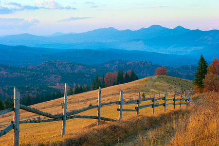 Autumn evening in mountains Carpathians, around the forest, field and clouds in the sky photo
