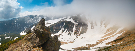 rock in the middle Carpathians around snow and dry grass on a background of clouds and blue sky photo
