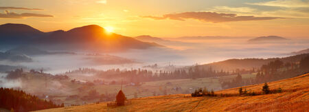 sunrise, mountain village in the fog and everything nice in yellow light photo