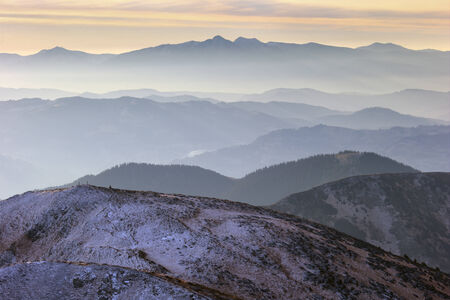 many hills in the fog in the background high mountain range, is covered with light snow photo