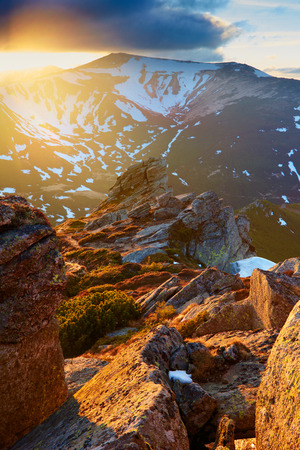 dramatic light of a morning in mountains Carpathians; rock illuminated red light;