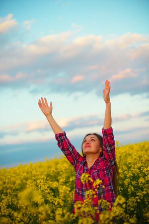 Girl in rape, yellow flowers, yellow sunlight Stock Photo