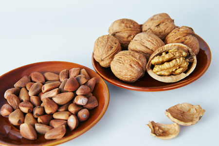 walnuts and pine nuts on a white background lie in a beautiful plate.
