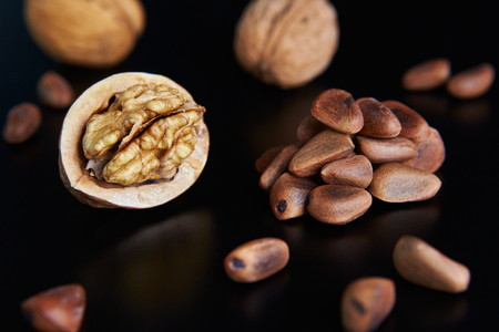 walnuts and pine nuts on a black background