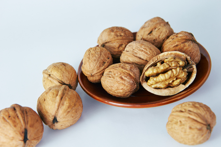 Greek nuts on a white background, lying in a beautiful plate Imagens