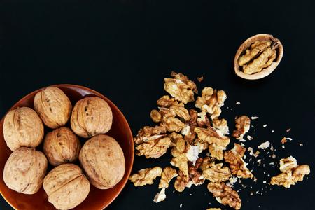 Greek walnuts on a black background, lie in a beautiful bowl