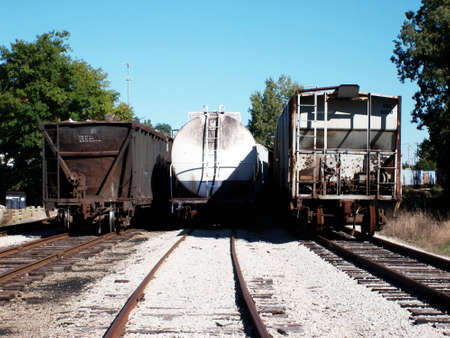 tanker type: A photo showing three train cars from behind, each a different type of car including a coal carrier, a tanker, and a boxcar. Stock Photo