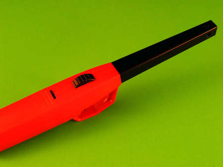 butane: An extended safety lighter against a green background. Stock Photo