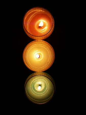 Three candles; one each of red, yellow, and green; in a column against a dark background.