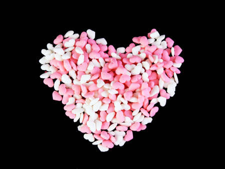 A heart made from candy hearts against a black background.
