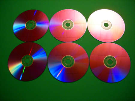 reflect: Six compact discs lit in such a way as to reflect a multitude of colors. Stock Photo