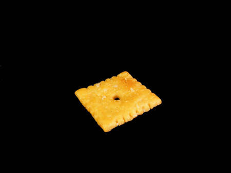 A cheese cracker against a black background. Фото со стока