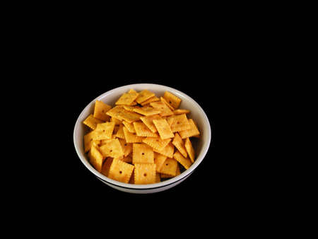 A bowl of cheese crackers against a black background.