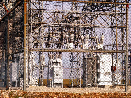 An electrical substation behind a fence. Imagens