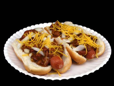 Two chili dogs with cheese and onions on a paper plate against a black background. photo