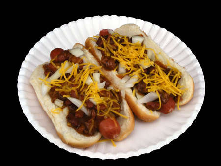 Two chili dogs with cheese and onions on a paper plate against a black background.