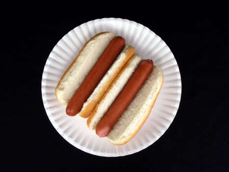 A pair of hot dogs on a paper plate against a black background.