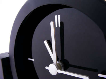 A black clock with silver hands set to eleven oclock.