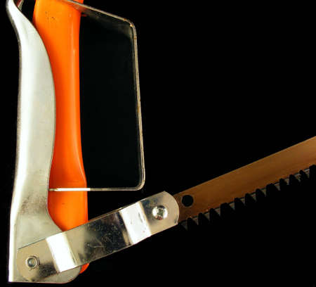 An orange hacksaw handle and blade against a black background.