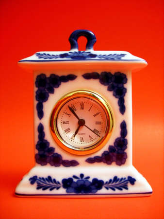 A simple, inexpensive white porcelain clock with blue flowers. Shot against an orange background. Stock fotó