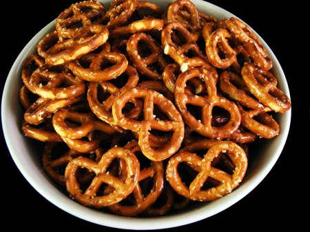 A bowl of pretzels shot against a black background.