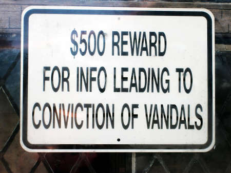 conviction: A window sign offering a reward for information leading to the conviction of vandals