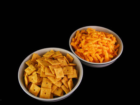 Bowls of cheese snacks and cheese crackers against a black background. Reklamní fotografie