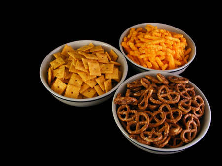Bowls of cheese snacks, pretzels and cheese crackers against a black background.