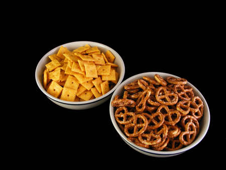 Bowls of pretzels and cheese crackers against a black background.