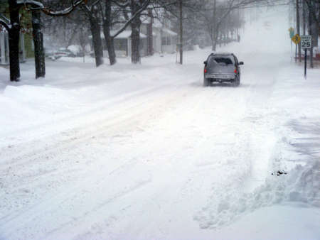 A SUV driving on a snow-packed road.