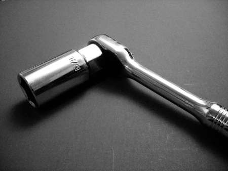 socket wrench: A stark black and white image of a socket wrench with a spark plug socket attached.
