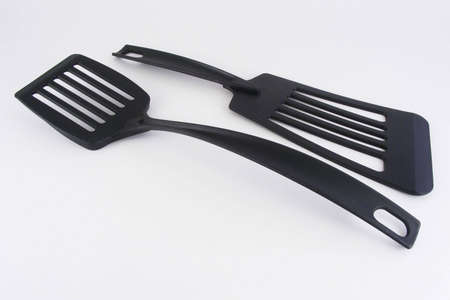 Two black nylon spatulas against an off-white background.