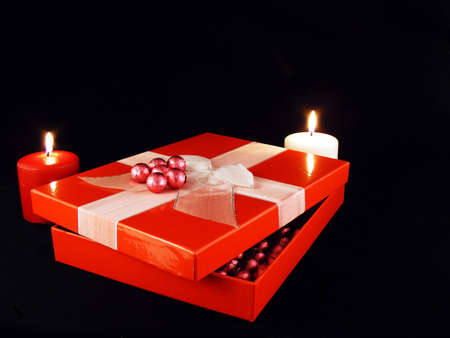 A valentines gift with candles against a black background.