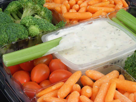 A vegetable snack tray with dip, carrots, broccoli, celery and tomatoes.