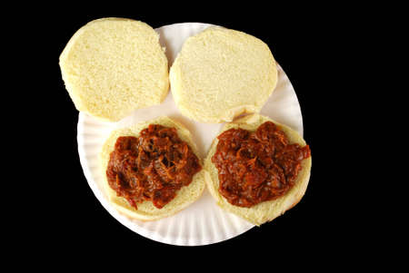 Two barbecue beef sandwiches on a paper plate against a black background.