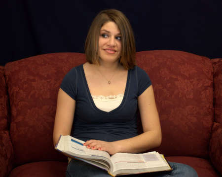 A pretty teenage girl sitting on a sofa studying a textbook.