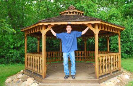 A young man standing in a wooden gazebo.