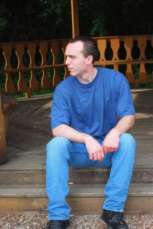 A young man sitting on a wooden step. Imagens