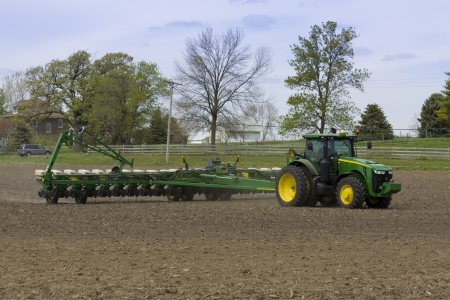 seed drill: Huge Tractor in Action Sowing with Trees in Background