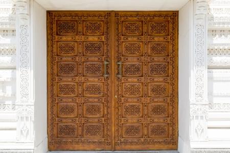 door knob: ornated wooden front door in a hindu temple Stock Photo