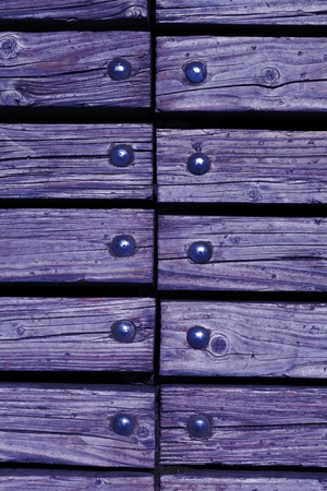 rivets: purple wooden texture background with rivets close up