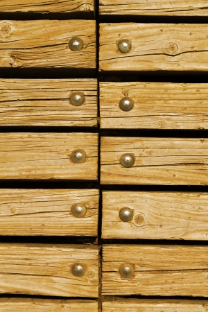 rivets: light orange wooden texture background with rivets close up