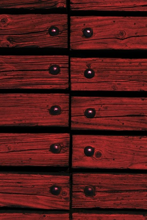 carmine: carmine red wooden texture background with rivets close up