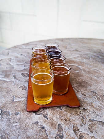 beer flight of eight sampling glasses on a serving paddle