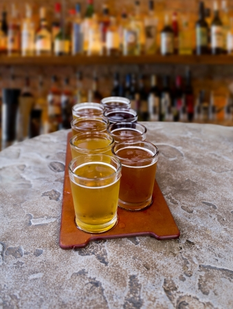 beer flight of eight sampling glasses on a serving paddle in a bar