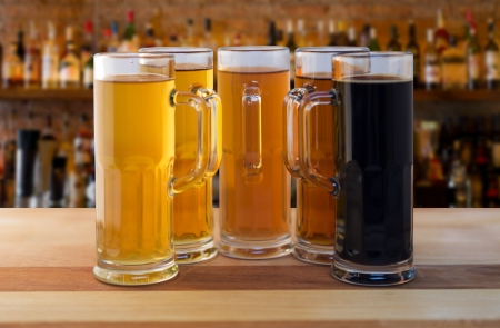 sampling: beer flight of five sampling mugs of light and dark craft beer in a bar