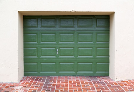 double green wooden garage door with paved driveway photo