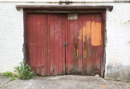 old damaged double red wooden garage door photo