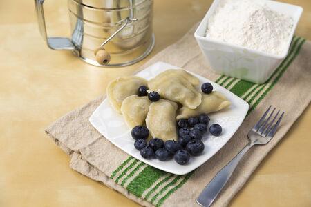 small plate full of Polish pierogi with blueberry filling photo