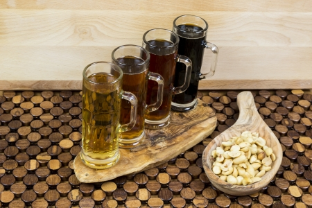 beer flight of four sampling mugs of light and dark craft beer with nuts